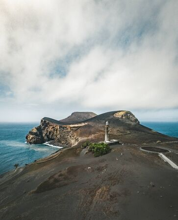 View over Capelinhos volcano, lighthouse of Ponta dos Capelinhos on western coast on Faial island, Azores, Portugal on a sunny day with blue sky and clouds and waves. Last volcano eruption was in 1957. Imagens