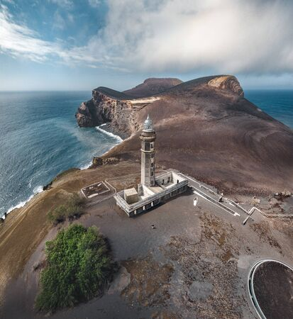 View over Capelinhos volcano, lighthouse of Ponta dos Capelinhos on western coast on Faial island, Azores, Portugal on a sunny day with blue sky and clouds and waves. Last volcano eruption was in 1957. Imagens - 127424704