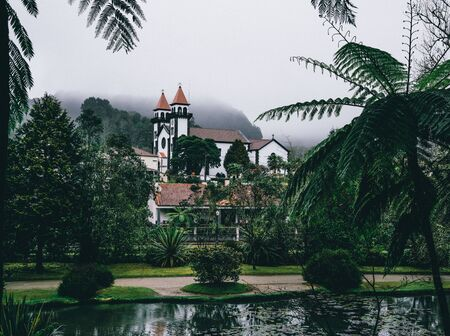 View towards Church of Furnas in Terra Nostra Garden Park on Sao Miguel island, Furnas, Azores. It is located in the midst of this magnificent water system. Imagens - 127424709
