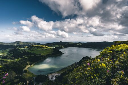 Panoramic landscape with aerial view on beautiful blue green crater lake Lagoa das Furnas and village Furnas with vulcanic thermal area. Sao Miguel, Azores, Portugal. Countryside landscape with green fields and blue sky and clouds.