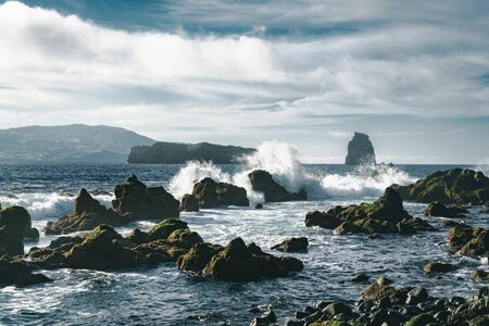 Azores, Big waves crashing over black volcanic rock on the Atlantic Ocean in the coast of Faial island in the Azores, Portugal