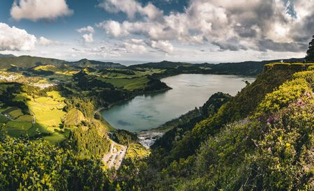 Panoramic landscape with aerial view on beautiful blue green crater lake Lagoa das Furnas and village Furnas with vulcanic thermal area. Sao Miguel, Azores, Portugal. Countryside landscape with green fields and blue sky and clouds. Photo taken in Azores, Portugal. Imagens - 127424899
