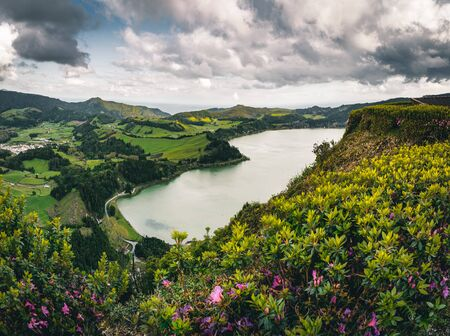 Panoramic landscape with aerial view on beautiful blue green crater lake Lagoa das Furnas and village Furnas with vulcanic thermal area. Sao Miguel, Azores, Portugal. Countryside landscape with green fields and blue sky and clouds. Imagens - 127424901