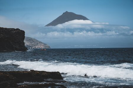 Mount Pico volcano western slope viewed from ocean with summit in clouds, seen from Faial Island in Azores, Portugal.