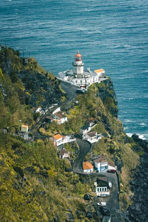 Dramatic view down to lighthouse on Ponta do Arnel, Nordeste, Sao Miguel Island, Azores, Portugal Imagens - 127424909