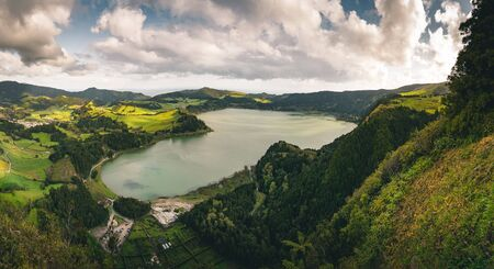 Panoramic landscape with aerial view on beautiful blue green crater lake Lagoa das Furnas and village Furnas with vulcanic thermal area. Sao Miguel, Azores, Portugal. Countryside landscape with green fields and blue sky and clouds. Imagens - 128737203