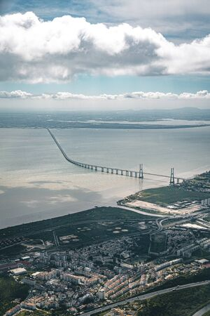 Aerial panorama view over the 25 de Abril Bridge. The bridge is connecting the city of Lisbon to the municipality of Almada on the left bank of the Tejo river, Lisbon Stock Photo - 132494615