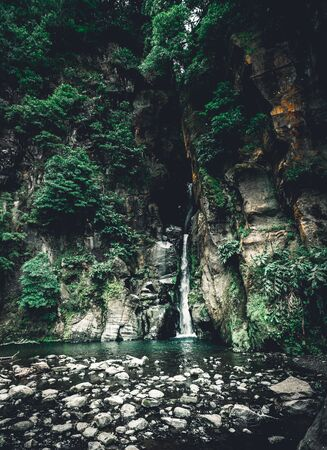 Salto do Cabrito beautiful waterfall at hiking trail falling a from rock cave in green forest, Sao Miguel, Ribeira Grande, Azores, Portugal