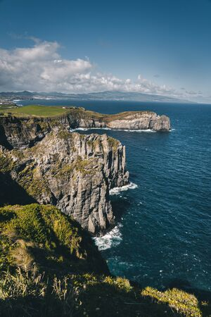 Lookout from Ponta do Cintrao at cliffs and coastline in sunny weather with beautiful cloudy blue sky, Sao Miguel Island, Azores Imagens