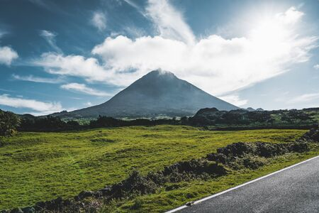 Straight EN3 longitudinal road northeast of Mount Pico and the silhouette of the Mount Pico along , Pico island, Azores, Portugal. Imagens - 128913370