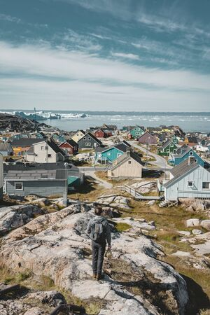 Aerial View of Arctic city of Ilulissat, Greenland. Colorful houses in the center of the town with icebergs in the background in summer on a sunny day with blue sky and clouds