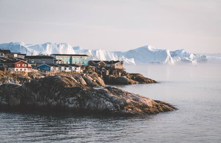 Aerial View of Arctic city of Ilulissat, Greenland during sunrise sunset with fog. Colorful houses in the center of the town with icebergs in the background in summer on a sunny day with orange pink sky