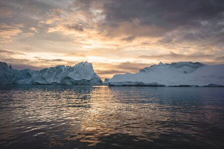 Arctic nature landscape with icebergs in Greenland icefjord with midnight sun sunset sunrise in the horizon. Early morning summer alpenglow during midnight season. Ilulissat, West Greenland. Imagens