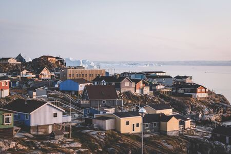Aerial View of Arctic city of Ilulissat, Greenland during sunrise sunset with fog. Colorful houses in the center of the town with icebergs in the background in summer on a sunny day with orange pink sky. Photo taken in Greenland.