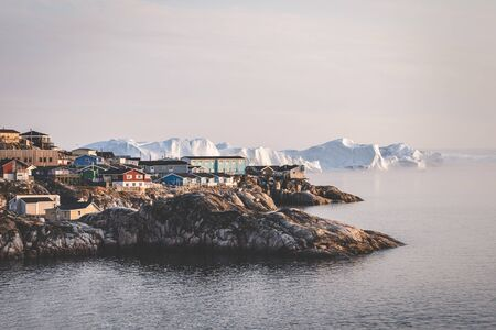 Aerial View of Arctic city of Ilulissat, Greenland during sunrise sunset with fog. Colorful houses in the center of the town with icebergs in the background in summer on a sunny day with orange pink sky. Photo taken in Greenland. Stock Photo - 132591112