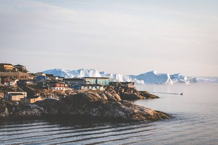 Aerial View of Arctic city of Ilulissat, Greenland during sunrise sunset with fog. Colorful houses in the center of the town with icebergs in the background in summer on a sunny day with orange pink sky. Photo taken in Greenland. Stock Photo - 132591142