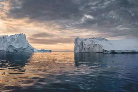 Arctic nature landscape with icebergs in Greenland icefjord with midnight sun sunset sunrise in the horizon. Early morning summer alpenglow during midnight season. Ilulissat, West Greenland. Photo taken in Greenlannd. Stock Photo - 132591515