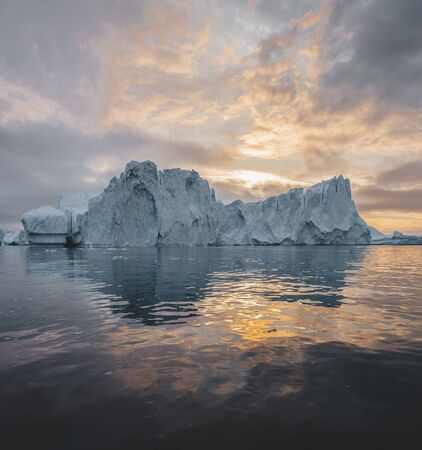 Arctic nature landscape with icebergs in Greenland icefjord with midnight sun sunset sunrise in the horizon. Early morning summer alpenglow during midnight season. Ilulissat, West Greenland. Photo taken in Greenlannd. Stock Photo - 132603168