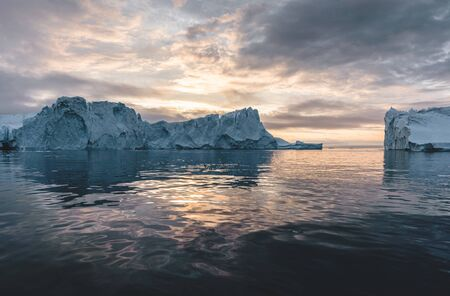 Arctic nature landscape with icebergs in Greenland icefjord with midnight sun sunset sunrise in the horizon. Early morning summer alpenglow during midnight season. Ilulissat, West Greenland. Photo taken in Greenlannd.