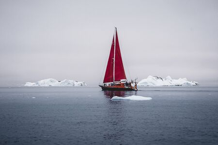 A small boat among icebergs. Sailboat cruising among floating icebergs in Disko Bay glacier during midnight sun Ilulissat, Greenland. Studying of a phenomenon of global warming Ices and icebergs