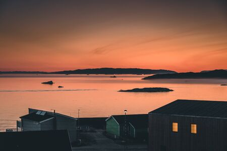 Aerial View of Arctic city of Ilulissat, Greenland during sunrise sunset. Colorful houses in the center of the town with icebergs in the background in summer on a sunny day with orange pink sky. Photo taken in Greenland.