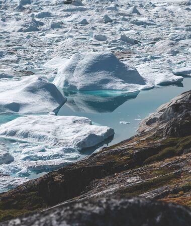 Blick Richtung Eisfjord in Ilulissat. Eisberge vom Kangia-Gletscher in Grönland schwimmen mit blauem Wasser. Symbol der globalen Erwärmung. Standard-Bild