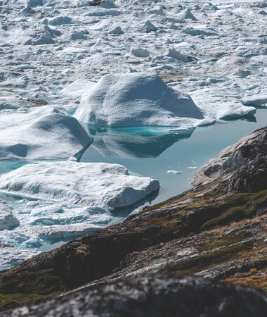 View towards Icefjord in Ilulissat. Icebergs from Kangia glacier in Greenland swimming with blue water. Symbol of global warming.