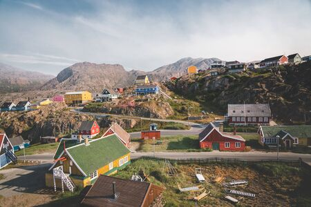 Colourful little Arctic town Sisimiut in Greenland,Qeqqata Municipality, aka Holsteinsborg . Second largest city in Greenland. Overview of port area and Sisimiut Museum, a collection of historic buildings. Blue sky with clouds and mountain in background.