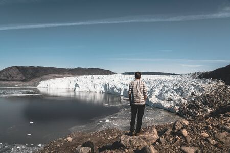 A young man traveler tourist standing in front of Eqip Sermia glacier called Eqi Glacier. Wall of ice in background. The concept of global warming and professional guides. On a sunny day with blue sky. Banco de Imagens