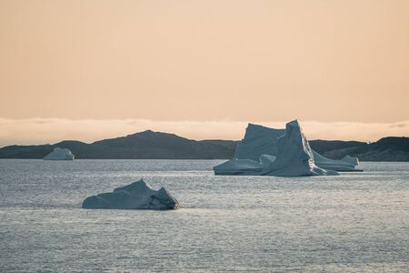 Iceberg at sunset. Nature and landscapes of Greenland. Disko bay. West Greenland. Summer Midnight Sun and icebergs. Big blue ice in icefjord. Affected by climate change and global warming. Foto de archivo