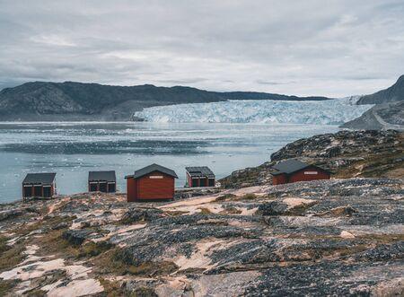 Imagen panorámica del campamento Eqi en el glaciar Eqip Sermia en Groenlandia. paisaje natural con cabañas lodge. Sol de medianoche y cielo rosa. Destino turístico glaciar Eqi en el oeste de Groenlandia también conocido como Ilulissat y glaciar Jakobshavn. Muy afectado por el calentamiento global. Foto tomada en Groenlandia Foto de archivo
