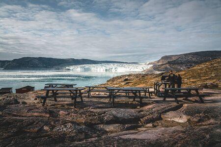 Imagen panorámica del campamento Eqi en el glaciar Eqip Sermia en Groenlandia. paisaje natural con cabañas lodge. Sol de medianoche y cielo rosa. Destino turístico glaciar Eqi en el oeste de Groenlandia también conocido como Ilulissat y glaciar Jakobshavn. Muy afectado por el calentamiento global. Foto tomada en Groenlandia