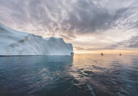 Beautiful red sailboat in the arctic next to a massive iceberg showing the scale. Cruising among floating icebergs in Disko Bay glacier during midnight sun season of polar summer Ilulissat, Disko Bay, Greenland. Photo taken in Greenland.
