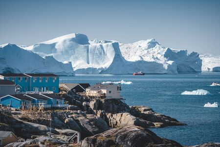 Aerial View of Arctic city of Ilulissat, Greenland. Colorful houses in the center of the town with icebergs in the background in summer on a sunny day with blue sky and clouds. Photo taken in Greenland.