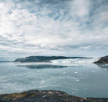 Imagen panorámica del campamento Eqi en el glaciar Eqip Sermia en Groenlandia. paisaje natural con cabañas lodge. Sol de medianoche y cielo rosa. Destino turístico glaciar Eqi en el oeste de Groenlandia también conocido como Ilulissat y glaciar Jakobshavn. Muy afectado por el calentamiento global.