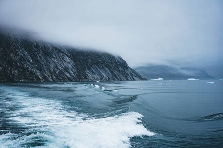Waves crashing at the shore on an overcast day in the arctic circle in Greenland. Powerful ocean waves breaking.Wave breaks on a shallow bank. Natural background with clouds hanging low in the mountains. Photo taken in Greenland.