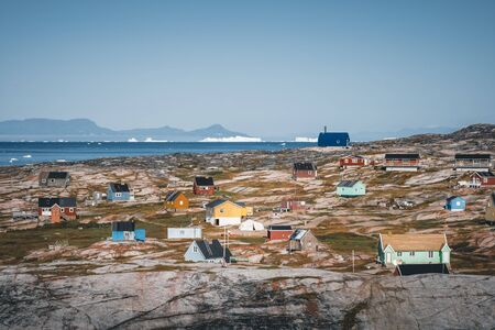 Typical wooden colourful blue fisher house with iceberg in Disko bay area Greenland and Ilulissat. Typical architecture in the arctic circle. Summer and blue sky.