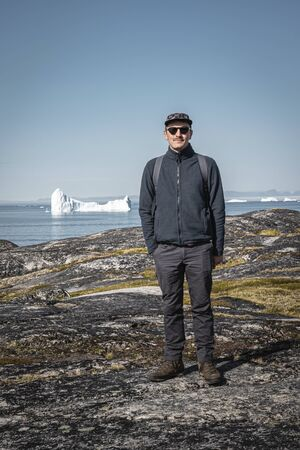Young man tourist standing in front of iceberg. View towards Icefjord in Ilulissat. Icebergs from Kangia glacier in Greenland swimming with blue sky and clouds. Symbol of global warming. 스톡 콘텐츠