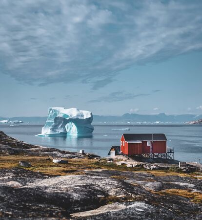 Iceberg with an arch in Antarctic Greenland waters against the backdrop of the mountains of the Arctic Peninsula. Small colourful houses on a sunny day with blue sky and clouds.