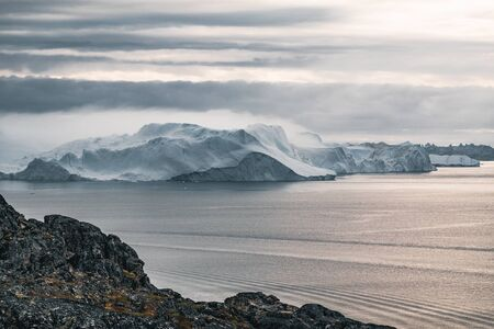 Arctic nature landscape with icebergs in Greenland icefjord. During midnight when sunset and sunrise meet in the horizon. Early morning summer alpenglow during midnight season. Ilulissat, West Greenland. Banque d'images