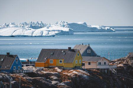 Vue aérienne de la ville arctique d'Ilulissat, au Groenland. Maisons colorées au centre de la ville avec des icebergs en arrière-plan en été par une journée ensoleillée avec ciel bleu et nuages
