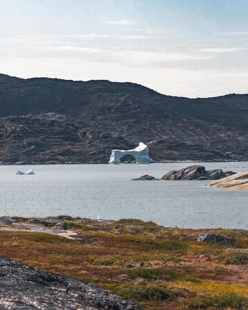 Magical arcticlandscape by Arctic Ocean in Greenland. Icebergs swimming in water. Blue sky on a summer day. Photo taken in Greenland.