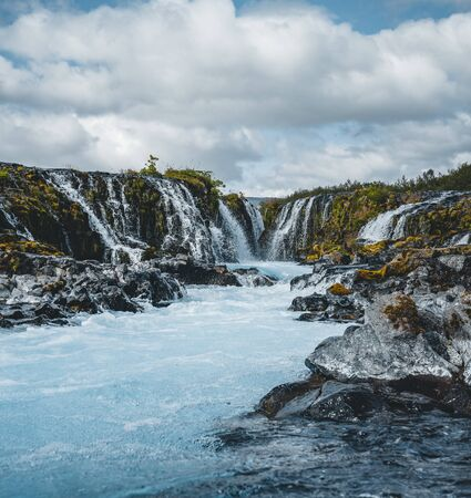 Dramatic views of the bright powerful Bruarfoss bluw waterfall. Popular tourist attraction. Blue sky and clouds during midnight sun. Location place Brekkuskogur South Iceland, Europe.
