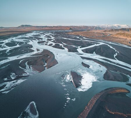 Aerial drone photograph image of a glacial river system in the south of Iceland during midnight sun and sunset. Glacier riverbed, delta in Iceland.