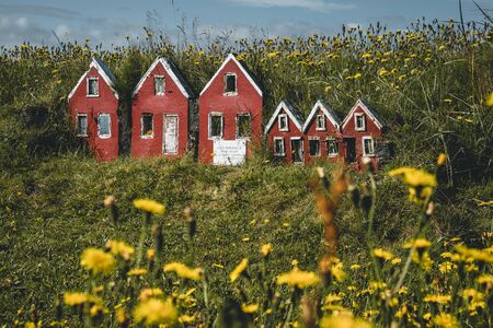 Trio of little red elf houses Hulduf lk with turf roofs in Iceland. Green grass with yellow flowers. Photo taken in Iceland.
