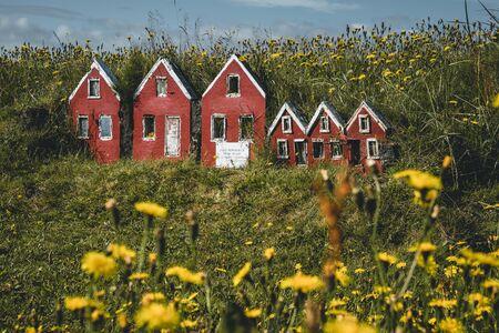 Trio małych czerwonych elfów Hulduf lk z dachami torfowymi w Islandii. Zielona trawa z żółtymi kwiatami. Zdjęcie zrobione w Islandii.