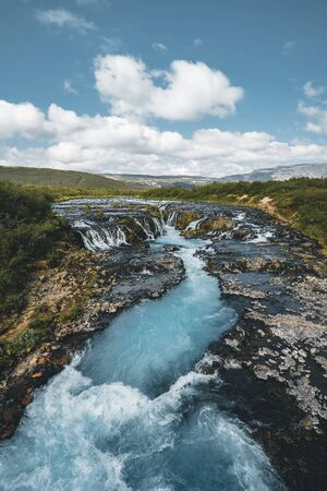 Incredible view of Bruarfoss Waterfall. The Iceland s Bluest Waterfall. Blue water flows over stones. Midnight sun of Iceland. Visit Iceland. Beauty world.