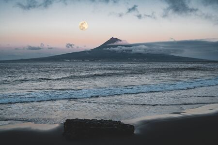 Mount Pico volcano western slope viewed from ocean during full moon with summit in clouds after sunset with pink sky, seen from Faial Island in Azores, Portugal. Photo taken in Azores, Portugal.