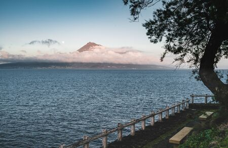 Pico Island, Azores, Portugal, with a view to Pico Mountain and wine culture between clouds during Sunset. Photo taken in Azores, Portugal.