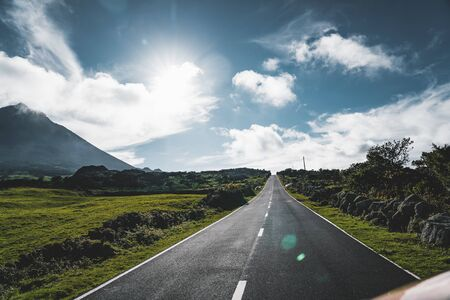 Straight EN3 longitudinal road northeast of Mount Pico and the silhouette of the Mount Pico along , Pico island, Azores, Portugal. Photo taken in Azores, Portugal. 版權商用圖片